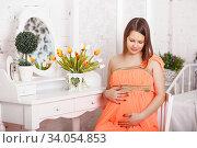 Купить «Happy elegant Pregnant woman hugging her belly», фото № 34054853, снято 13 декабря 2015 г. (c) Nataliia Zhekova / Фотобанк Лори
