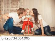 Mom and Dad kiss their little son. Стоковое фото, фотограф Nataliia Zhekova / Фотобанк Лори