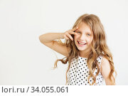 Lovely little girl in a polka-dot dress against a white background. Стоковое фото, фотограф Nataliia Zhekova / Фотобанк Лори