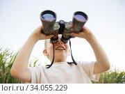 Little boy looking through binoculars on river bank. Стоковое фото, фотограф Nataliia Zhekova / Фотобанк Лори