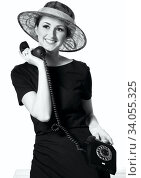 Portrait of a beautiful brown-eyed woman in a little black dress with a vintage telephone. Стоковое фото, фотограф Nataliia Zhekova / Фотобанк Лори
