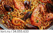 Купить «Spanish paella with prawns, calamari and mussels prepared in large frying pan», видеоролик № 34055633, снято 21 июня 2020 г. (c) Яков Филимонов / Фотобанк Лори