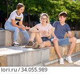 Купить «Teenagers friendly discussing and using phones outdoors», фото № 34055989, снято 3 августа 2020 г. (c) Яков Филимонов / Фотобанк Лори