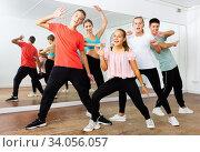 Cheerful teenage boys and girls having fun in choreography class, posing with female trainer. Стоковое фото, фотограф Яков Филимонов / Фотобанк Лори