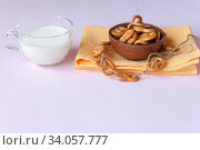 Pretzel cookies in a clay bowl on a yellow napkin and a clear mug of milk on a pink background. Стоковое фото, фотограф Катерина Белякина / Фотобанк Лори