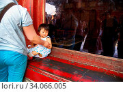 Купить «Ein Kleinkind sitzt in einem roten Fensterrahmen in der Verbotenen Stadt in Peking, China | A baby sits in on a red window frame in the Forbidden City in Beijing, China», фото № 34066005, снято 11 июля 2020 г. (c) easy Fotostock / Фотобанк Лори