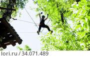 Купить «Rope adventure - woman walks on the suspension rope bridge», видеоролик № 34071489, снято 5 июля 2020 г. (c) Константин Шишкин / Фотобанк Лори