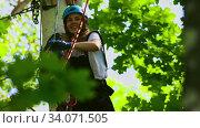 Купить «Rope adventure - smiling woman pulls a rope to herself», видеоролик № 34071505, снято 7 июля 2020 г. (c) Константин Шишкин / Фотобанк Лори