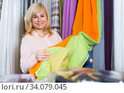 Купить «Mature woman customer choosing color curtains», фото № 34079045, снято 17 января 2018 г. (c) Яков Филимонов / Фотобанк Лори