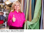 Купить «seller showing curtain and holding thumb up», фото № 34079069, снято 17 января 2018 г. (c) Яков Филимонов / Фотобанк Лори