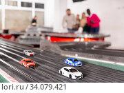 Men and women play with slot car racing track. Стоковое фото, фотограф Яков Филимонов / Фотобанк Лори
