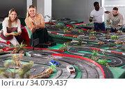 Couples play game slot car racing track. Стоковое фото, фотограф Яков Филимонов / Фотобанк Лори