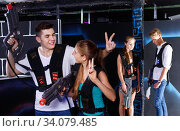 Girl and guy with laser pistols happy with their victory over opposing team in laser tag game in dark room. Стоковое фото, фотограф Яков Филимонов / Фотобанк Лори