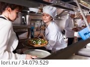 Female chef giving cooked pizza to waitress. Стоковое фото, фотограф Яков Филимонов / Фотобанк Лори