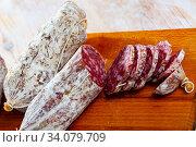 Italian cacciatori salami sausages on a wooden table. Стоковое фото, фотограф Яков Филимонов / Фотобанк Лори