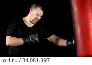 Young male boxer training on a punching bag in the gym, natural dark background. Стоковое фото, фотограф Zoonar.com/Serghei Starus / easy Fotostock / Фотобанк Лори