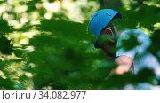 Купить «Man moving forward across the rope bridge in the forest on high - extreme rope bridge entertainment», видеоролик № 34082977, снято 12 июля 2020 г. (c) Константин Шишкин / Фотобанк Лори