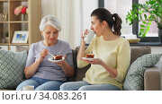 old mother and adult daughter eating cake at home. Стоковое видео, видеограф Syda Productions / Фотобанк Лори