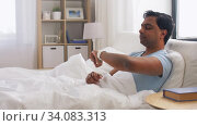 happy indian man with smart watch in bed at home. Стоковое видео, видеограф Syda Productions / Фотобанк Лори