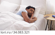 indian man awaking and stretching in bed at home. Стоковое видео, видеограф Syda Productions / Фотобанк Лори