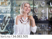Adult woman chooses jewelry from gemstone jewelery in the store. Стоковое фото, фотограф Яков Филимонов / Фотобанк Лори