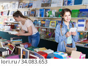Купить «glad girl chatting on screen tablet and choosing literature books with mother», фото № 34083653, снято 9 мая 2017 г. (c) Яков Филимонов / Фотобанк Лори