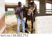 Young man farmer removes saddle from horse at stable at farm. Стоковое фото, фотограф Яков Филимонов / Фотобанк Лори