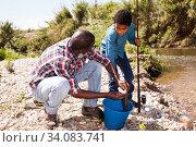 Купить «Man and boy with bucket of catch», фото № 34083741, снято 26 мая 2019 г. (c) Яков Филимонов / Фотобанк Лори