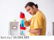 Купить «Young male contractor cleaning the house», фото № 34084489, снято 3 февраля 2020 г. (c) Elnur / Фотобанк Лори