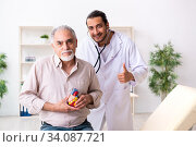 Old man visiting young male doctor cardiologist. Стоковое фото, фотограф Elnur / Фотобанк Лори