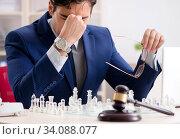 Купить «Young lawyer playing chess to train his court strategy and tacti», фото № 34088077, снято 31 июля 2018 г. (c) Elnur / Фотобанк Лори