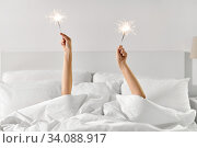 Купить «hands of woman lying in bed with sparklers», фото № 34088917, снято 22 января 2020 г. (c) Syda Productions / Фотобанк Лори