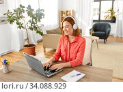 Купить «woman in headphones with laptop working at home», фото № 34088929, снято 29 марта 2020 г. (c) Syda Productions / Фотобанк Лори