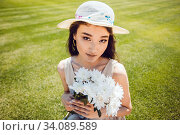 Portrait of a young asian woman in a hat. Woman holding a flower bouquet on nature background. Стоковое фото, фотограф Женя Канашкин / Фотобанк Лори