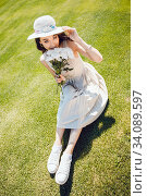Attractive young woman in a light dress and hat sits on the grass with a bouquet of flowers in her hands. Стоковое фото, фотограф Женя Канашкин / Фотобанк Лори