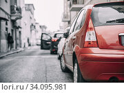 Купить «Cars Parked On Street In European City In Summer Day. All Colors Except Red Are Reduced.», фото № 34095981, снято 15 октября 2018 г. (c) easy Fotostock / Фотобанк Лори