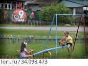 Дети катаются на качелях. Редакционное фото, фотограф Дмитрий Неумоин / Фотобанк Лори