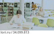 People reading and making notes while preparing for exam in library. Стоковое видео, видеограф Яков Филимонов / Фотобанк Лори