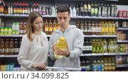 Купить «Portrait of friendly man and woman with shopping cart choosing olive oil in supermarket», видеоролик № 34099825, снято 30 июня 2020 г. (c) Яков Филимонов / Фотобанк Лори