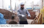 Focused young engineer planning renovation works at building site. Стоковое видео, видеограф Яков Филимонов / Фотобанк Лори