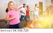 Купить «Girl exercising in group during dance class», фото № 34100725, снято 15 июля 2020 г. (c) Яков Филимонов / Фотобанк Лори
