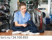 Купить «Worker of laundry checking clothes», фото № 34100893, снято 9 мая 2018 г. (c) Яков Филимонов / Фотобанк Лори