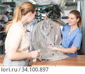 Купить «Worker of dry cleaner returning clean clothes», фото № 34100897, снято 9 мая 2018 г. (c) Яков Филимонов / Фотобанк Лори
