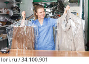 Купить «Girl worker showing clean clothing», фото № 34100901, снято 9 мая 2018 г. (c) Яков Филимонов / Фотобанк Лори