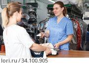 Купить «Worker of dry cleaner checking clothes on reception», фото № 34100905, снято 9 мая 2018 г. (c) Яков Филимонов / Фотобанк Лори