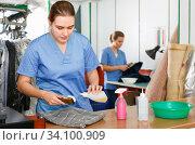 Купить «Two young women working in modern dry cleaner», фото № 34100909, снято 9 мая 2018 г. (c) Яков Филимонов / Фотобанк Лори