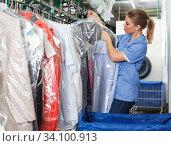Adult worker of laundry inspecting clothing. Стоковое фото, фотограф Яков Филимонов / Фотобанк Лори