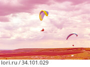 Купить «Russia, Samara Region, May 2020: A group of athletes fly on multi-colored paragliders against a bright cloudy sky on a sunny day.», фото № 34101029, снято 11 мая 2020 г. (c) Акиньшин Владимир / Фотобанк Лори