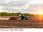 Купить «Russia Samara May 2020: Spring. Sowing work. A tractor with a seeder trailer works in the field at sunset.», фото № 34101033, снято 11 мая 2020 г. (c) Акиньшин Владимир / Фотобанк Лори