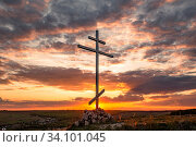 Купить «A large cross stands on a hill overlooking the steppe village against the backdrop of a picturesque sunset of the day.», фото № 34101045, снято 11 мая 2020 г. (c) Акиньшин Владимир / Фотобанк Лори